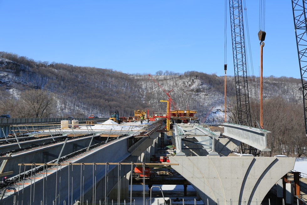 Delivery and placement of concrete girders at the Dresbach Bridge construction site.